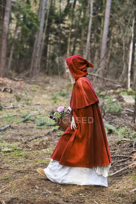 Girl masquerade as Red Riding Hood on the move in the wood — Stock Photo