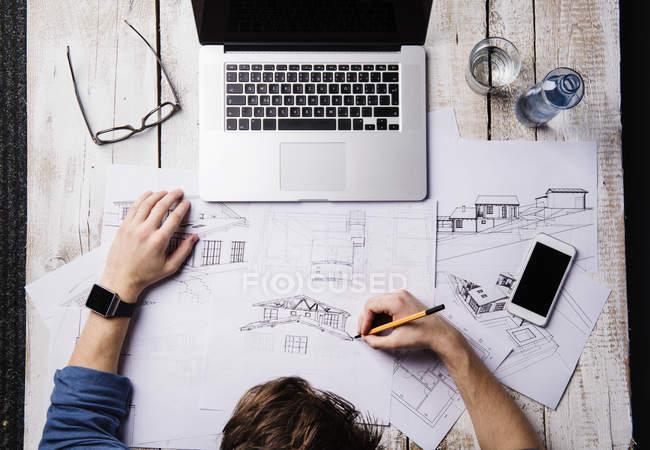 Architekt arbeitet am Schreibtisch mit Laptop, macht Skizzen — Stockfoto