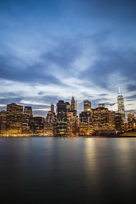 USA, New York, veduta da Brooklyn allo skyline illuminato di Manhattan e all'East River al crepuscolo della sera — Foto stock