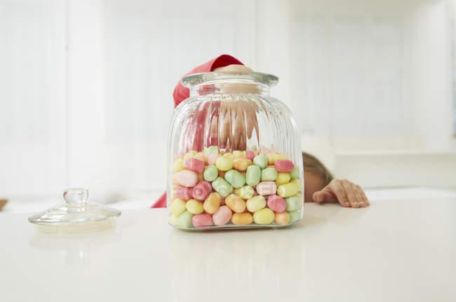 Girl beyond candy jar putting hand inside — Stock Photo