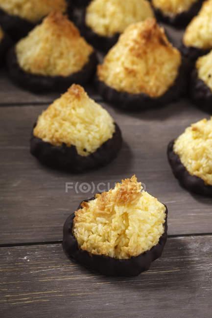 Macaroons de coco com cobertura de chocolate na madeira escura — Fotografia de Stock