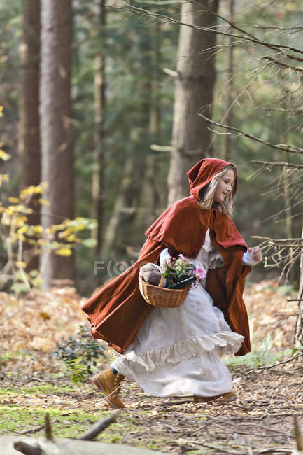 Girl masquerade as Red Riding Hood riunning in the wood — Stock Photo