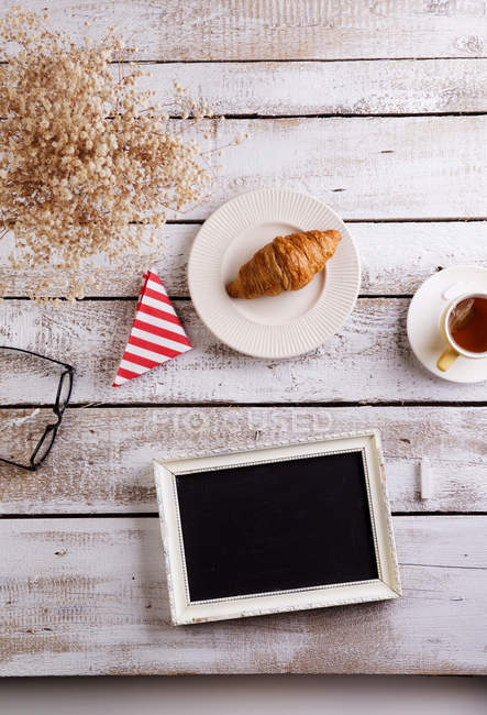 Table with croissant, tea and black board with copy space — Stock Photo