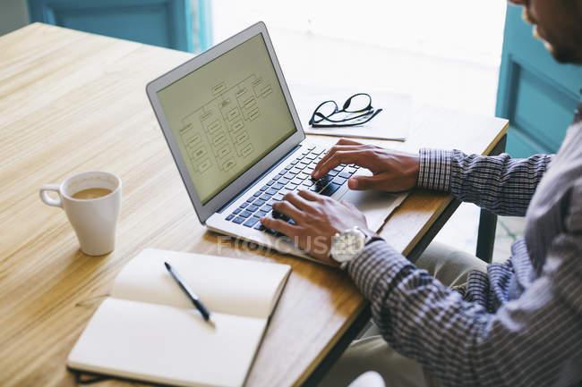 Крупный план человека с помощью ноутбука на рабочем столе в офисе — стоковое фото