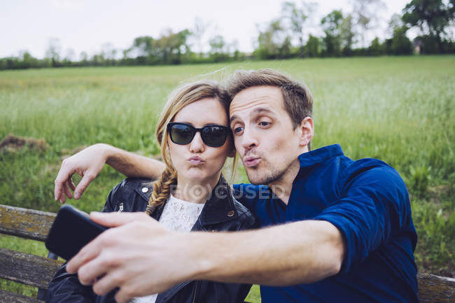 Portrait of couple pouting mouths taking selfie with smartphone — Stock Photo