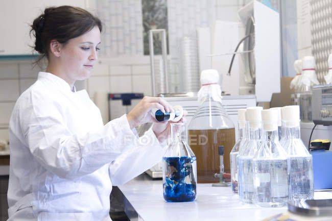Female food analyst working in laboratory — Stock Photo
