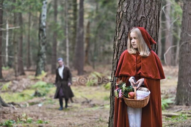 Girl masquerade as Red Riding Hood hiding behind a tree in the wood — Stock Photo