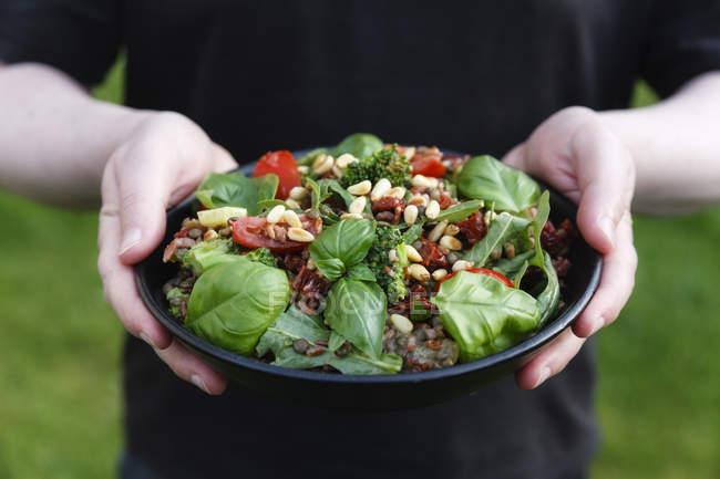 Человеческие руки держат миску с приготовленным рисовым салатом — стоковое фото