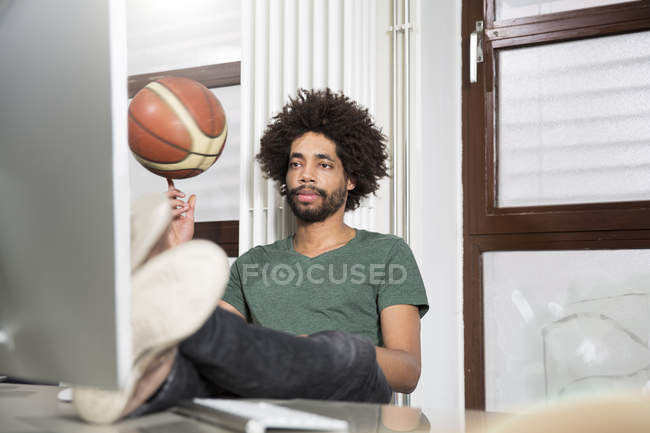 Creative professional balancing basketball at desk in office — Stock Photo