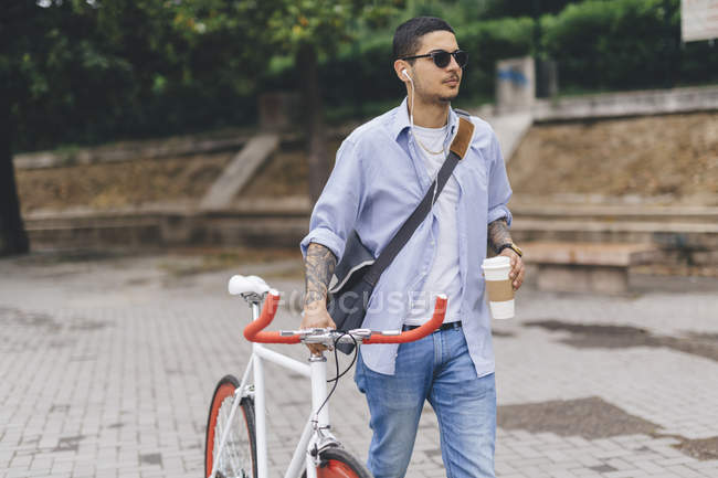 Young man walking with a bicycle in the city — Stock Photo