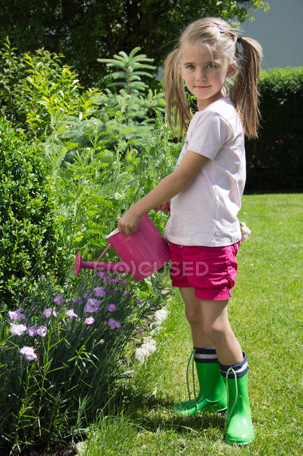 Portrait of little girl pouring plants with pink watering can in the garden — Stock Photo