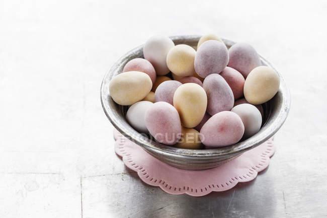 Пасхальные яйца в миске на розовом салфетке — стоковое фото