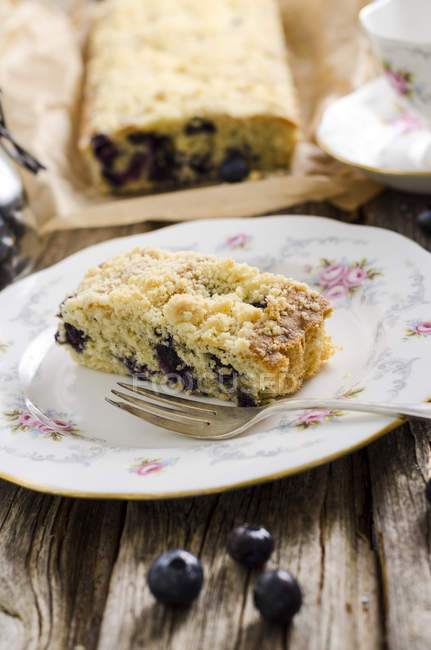 Кусок голубики раскрошить торт на плите на дереве — стоковое фото