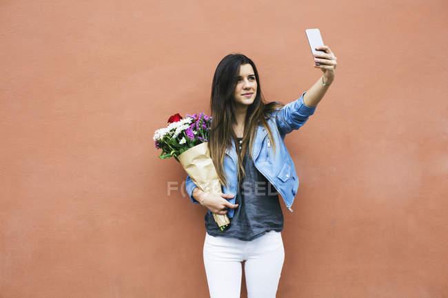 Jeune femme tenant le bouquet de fleurs et de prendre selfie avec smartphone — Photo de stock