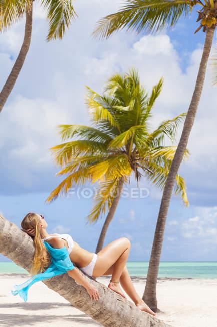 Домініканський Rebublic, молода жінка відпочинку на пальмових дерев з видом тропічний пляж — стокове фото