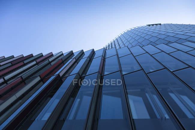 Dettaglio della moderna facciata in vetro contro il cielo — Foto stock