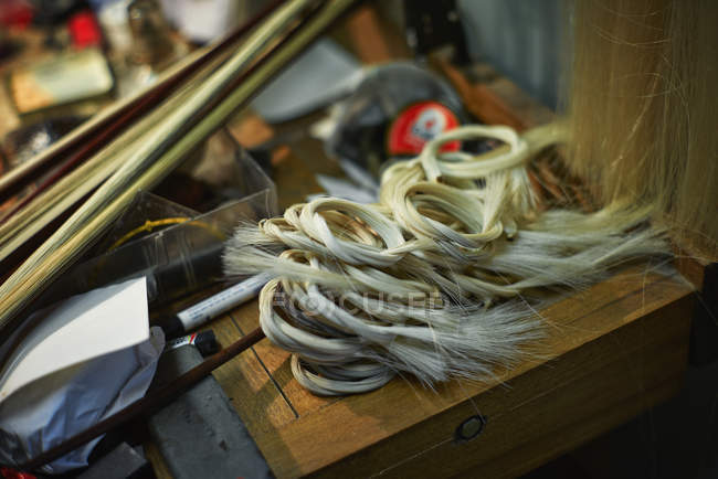 Tools and horsehair for the bows in a violin maker's workshop — Stock Photo
