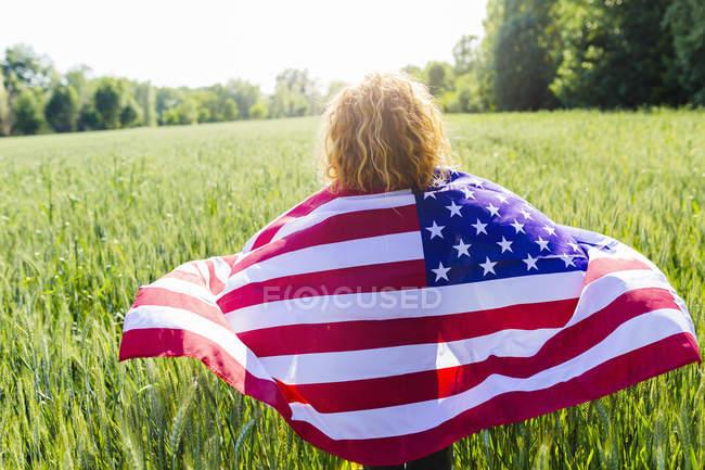 Vista posteriore della donna con bandiera americana in natura — Foto stock