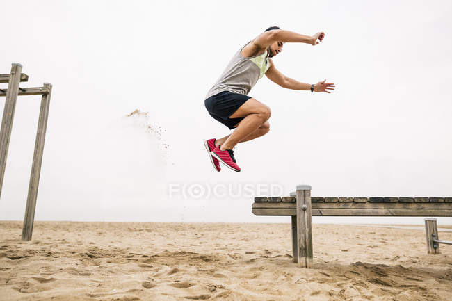 Young man training long jump on beach — Stock Photo