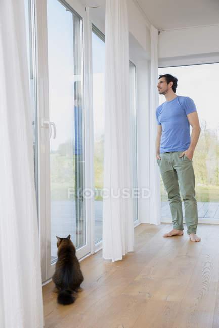 Homem em casa em pé na janela olhando para fora — Fotografia de Stock