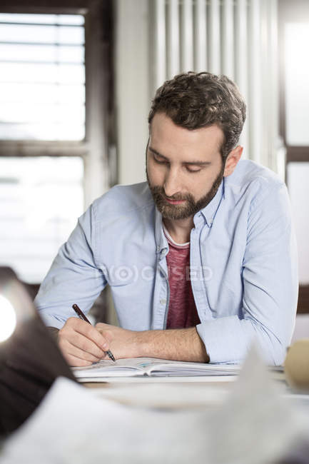 Creative professional working at desk with notebook — Stock Photo