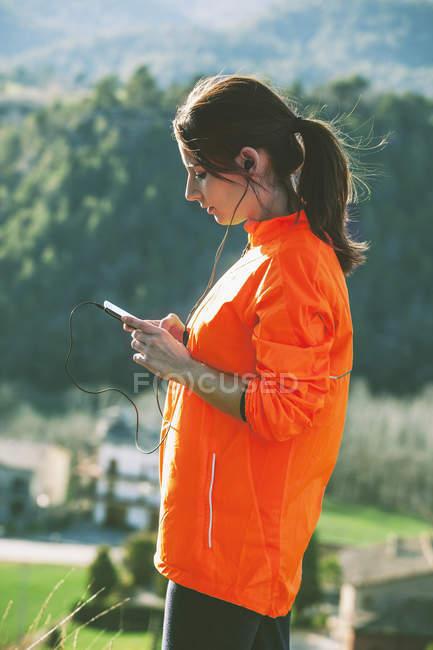 Joven jogger escuchando música con smartphone - foto de stock