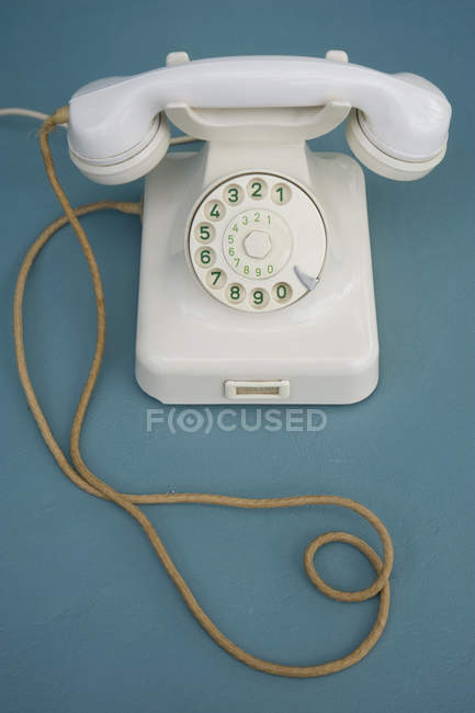 Old white bakelite telephone on green surface — Stock Photo