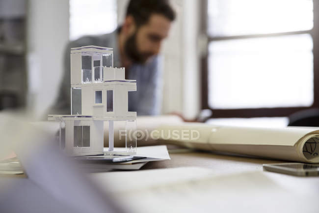 Desktop with architectural model and man on background — Stock Photo