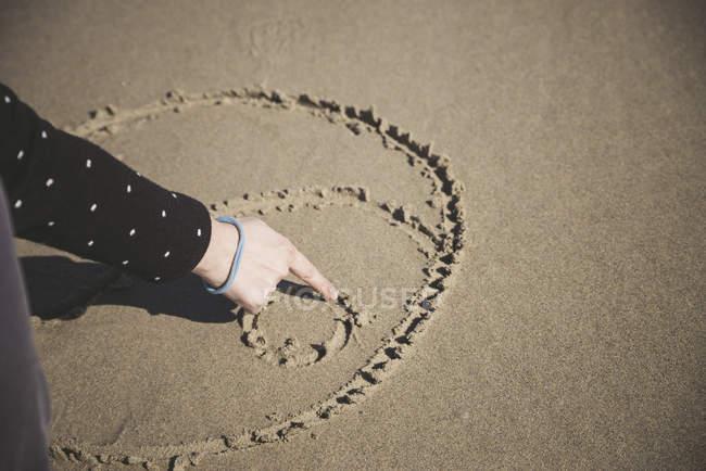 Mulher coçando o símbolo Yin Yang na areia de uma praia, close-up — Fotografia de Stock