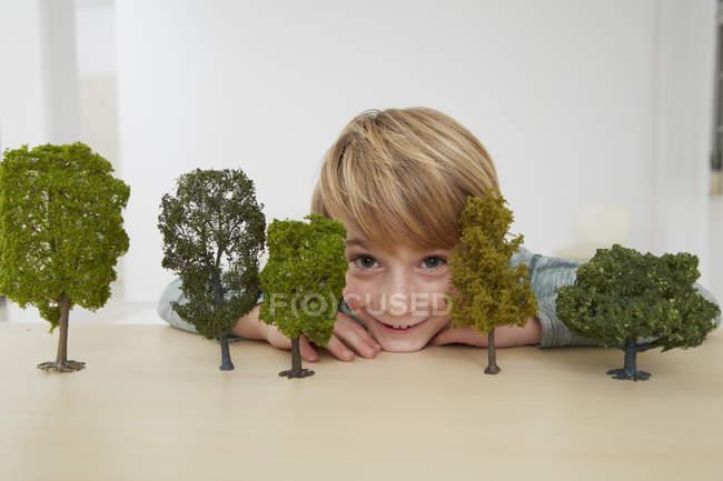 Garçon assis à table avec des modèles d'arbres, la conservation de l'environnement — Photo de stock