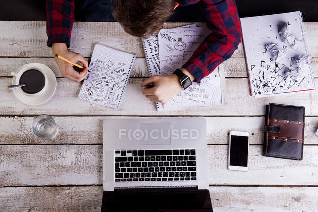 Man working at desk with laptop, making notes — Stock Photo
