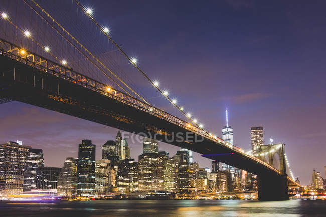 USA, New York City, lighted skyline and Brooklyn Bridge in the foreground at night — Stock Photo