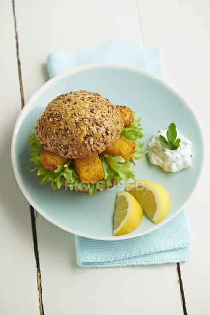 Бургер с пальцами рыбы и творога травы на синюю тарелку — стоковое фото