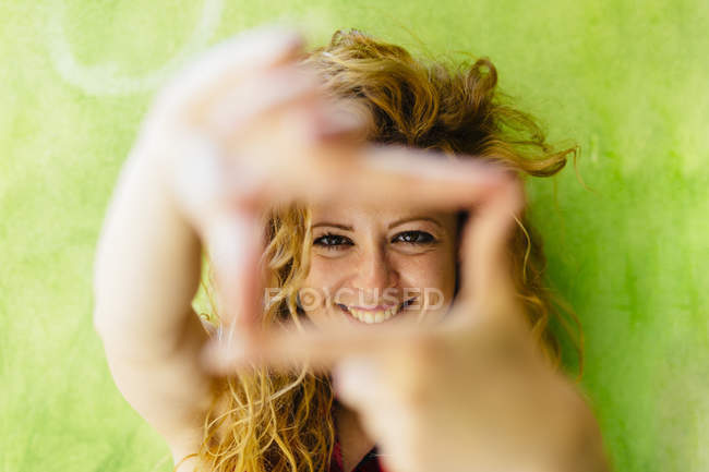 Портрет улыбающейся женщины, формирующей раму пальца — стоковое фото