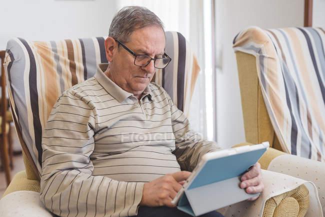 Senior man using digital tablet at home — Stock Photo