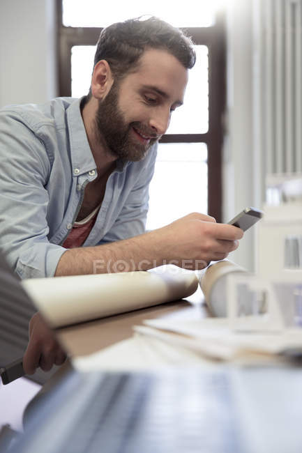 Creative professional using cell phone at desk — Stock Photo