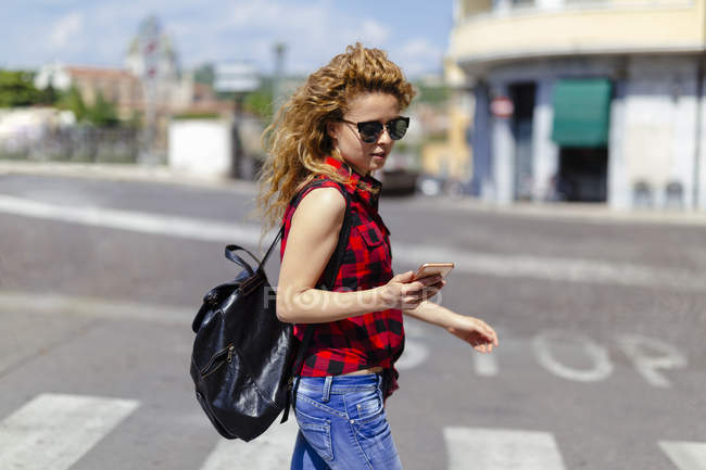 Italy, Verona, woman crossing street looking at cell phone — Stock Photo