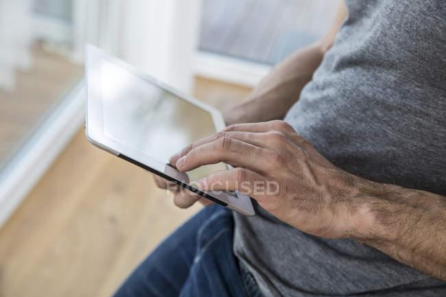 Uomo a casa con tablet digitale — Foto stock