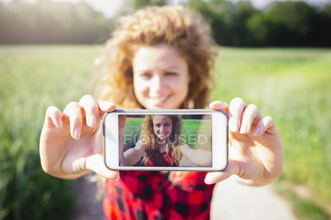 Selfie lächelnde Frau auf dem Display ihres Smartphones — Stockfoto