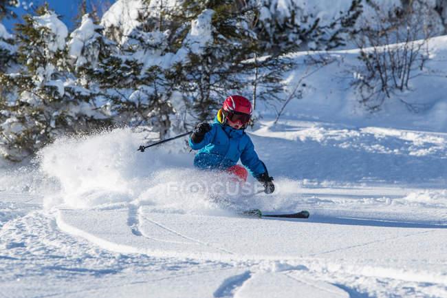 Ragazzo in casco e abbigliamento da sci sciare in giornata soleggiata sul pendio di montagna innevato — Foto stock