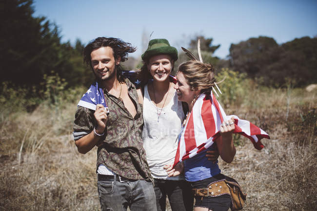 Три хиппи с американским флагом в природе — стоковое фото