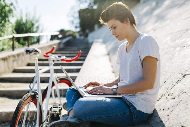 Young woman with bicycle sitting on tilted wall using laptop — Stock Photo