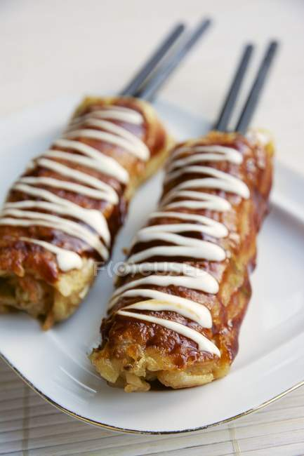 Hashimaki, Japanese savory cabbage pancakes on chopsticks — Stock Photo