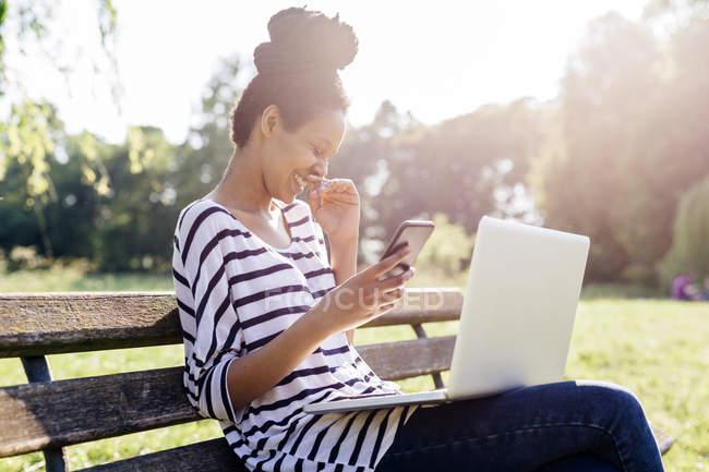 Rire jeune femme assise sur le banc du parc avec smartphone et ordinateur portable — Photo de stock