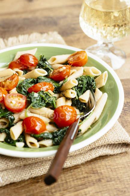 Prato de macarrão com espinafre e tomate — Fotografia de Stock