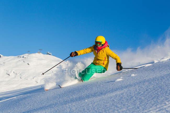 Femme ski sur la pente de la montagne enneigée en skiwear lumineux, casque et googles — Photo de stock