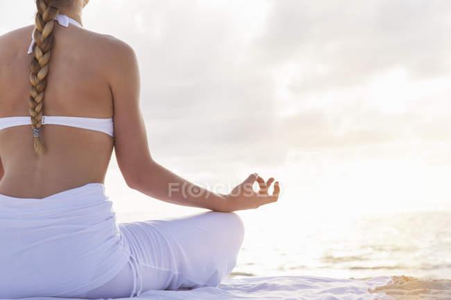 Молодая женщина делает упражнения йоги с видом на тропический пляж — стоковое фото