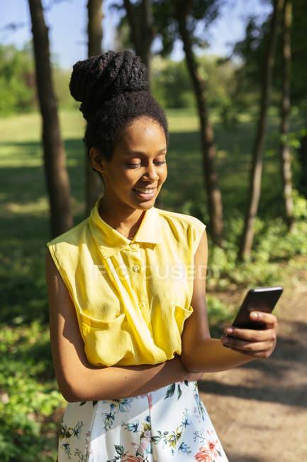Portrait de jeune femme souriante dans la nature regardant son smartphone — Photo de stock