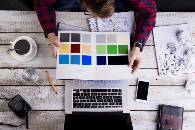 Mann arbeitet am Schreibtisch mit Laptop und betrachtet Proben — Stockfoto