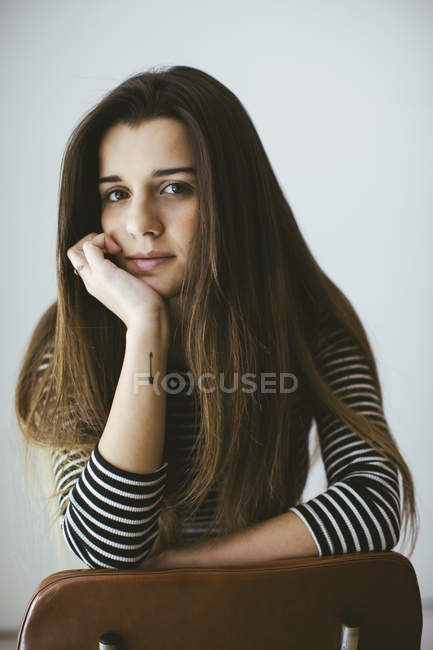 Young brunette woman leaning on chair and looking at camera — Stock Photo